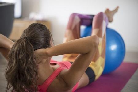 Žena cvičí brušné svaly s pomocou fitlopty.
