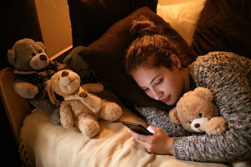 žena v posteli s mobilom