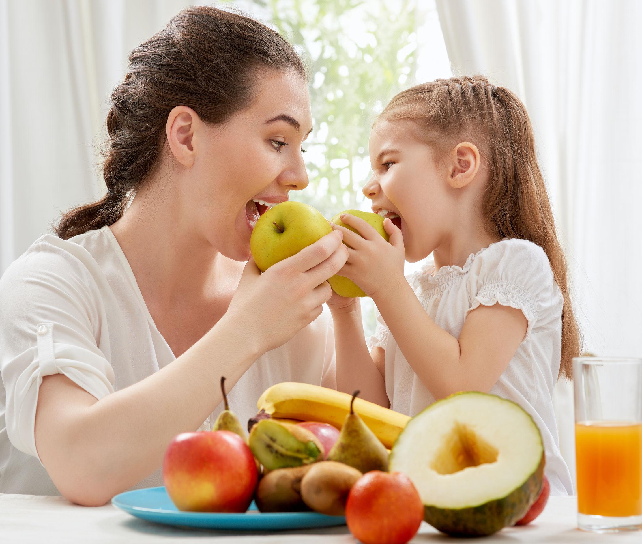 Matka s dieťaťom konzumujú jablko