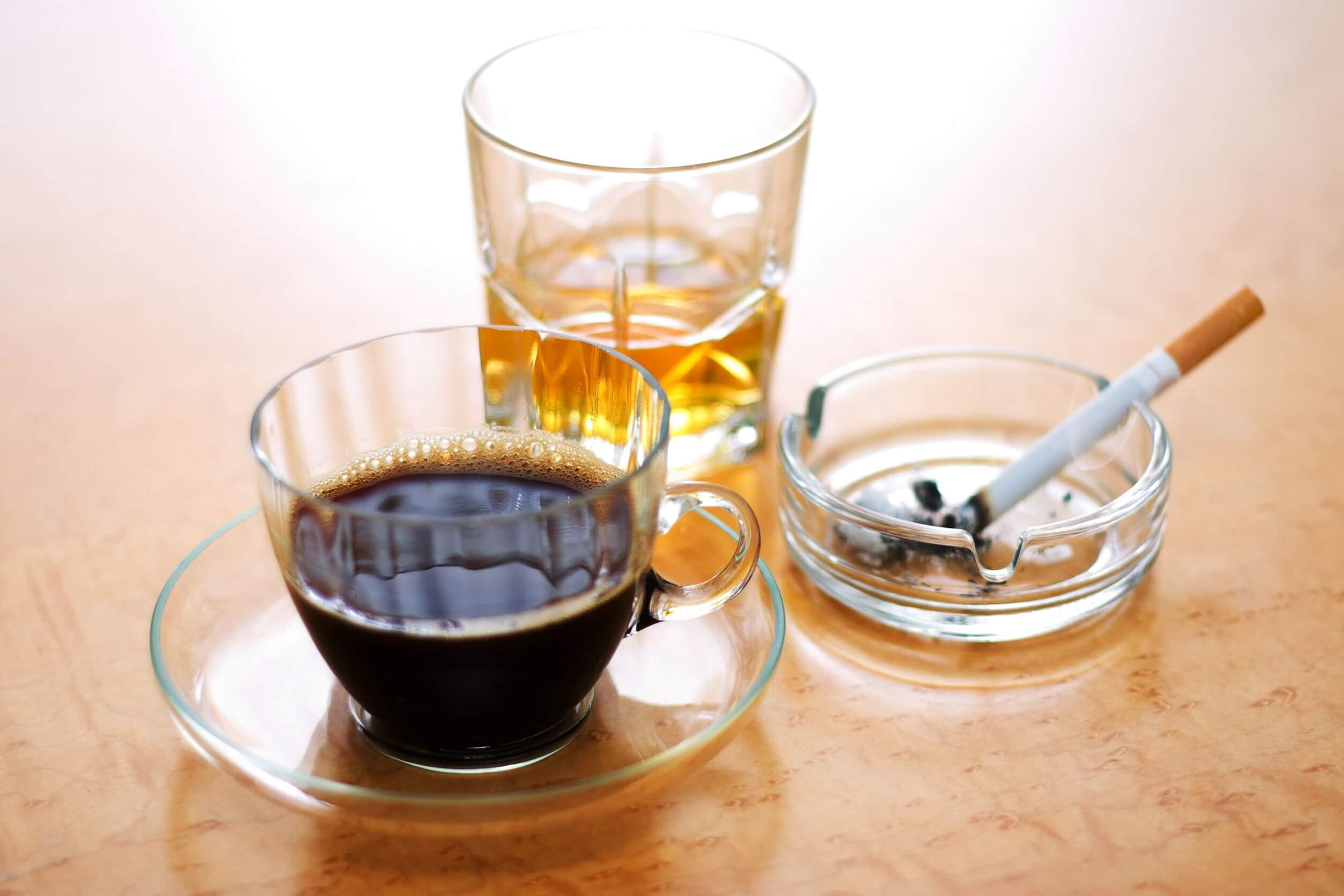 Šálka kávy, pohár s alkoholom a cigareta
