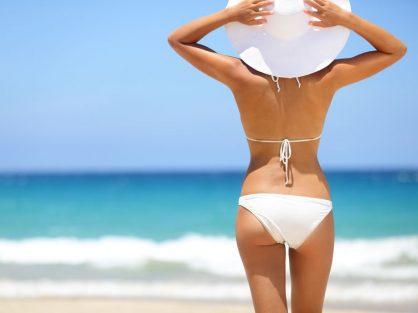 Žena v plavkách a klobúku pozerá na more