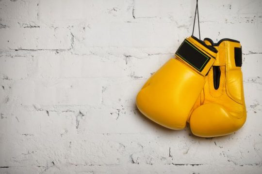 Žlté boxerské rukavice zavesené na stene