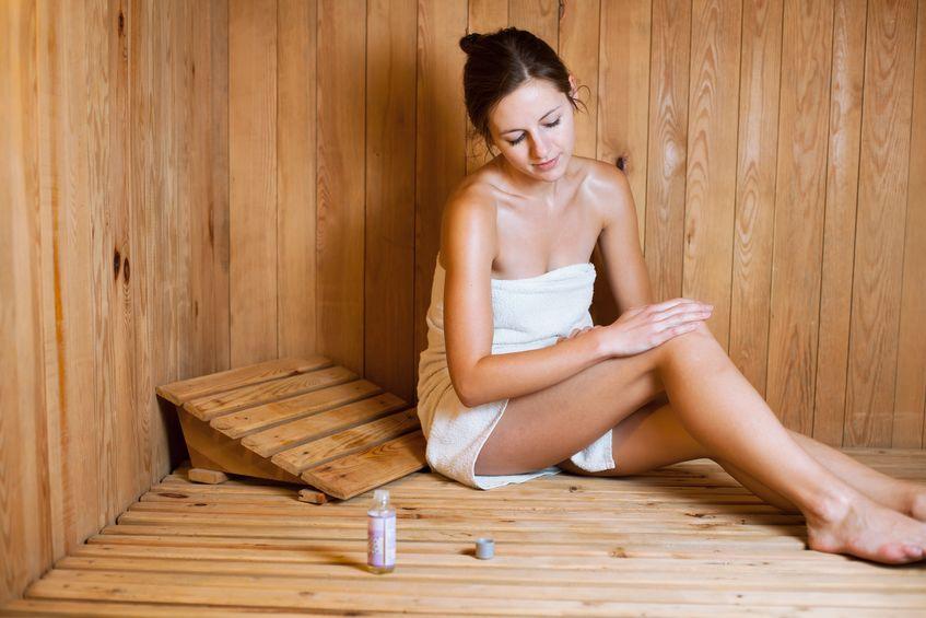 Žena v saune sa natiera olejom