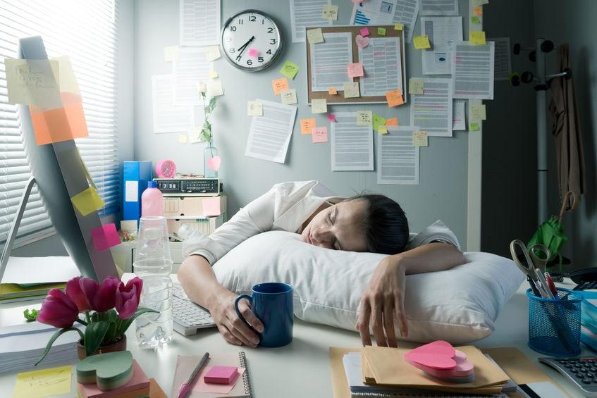 Žena ležiaca v práci kvôli nedostatku energie na vankúši na stole – únava je jedna z príčin nedostatku železa