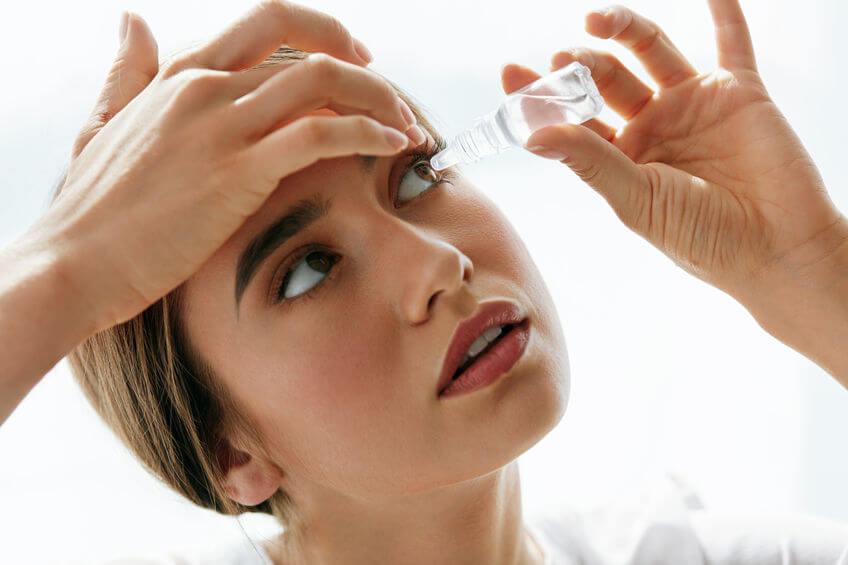 Žena si aplikuje kvapky do očí.