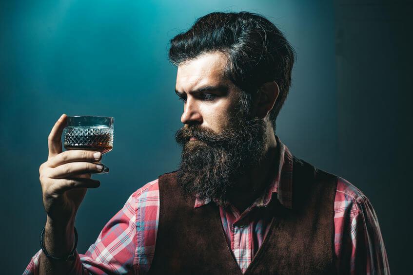 bradatý muž drží pohár whisky