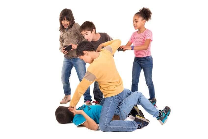 detská šikana chlapca bije spolužiak na zemi