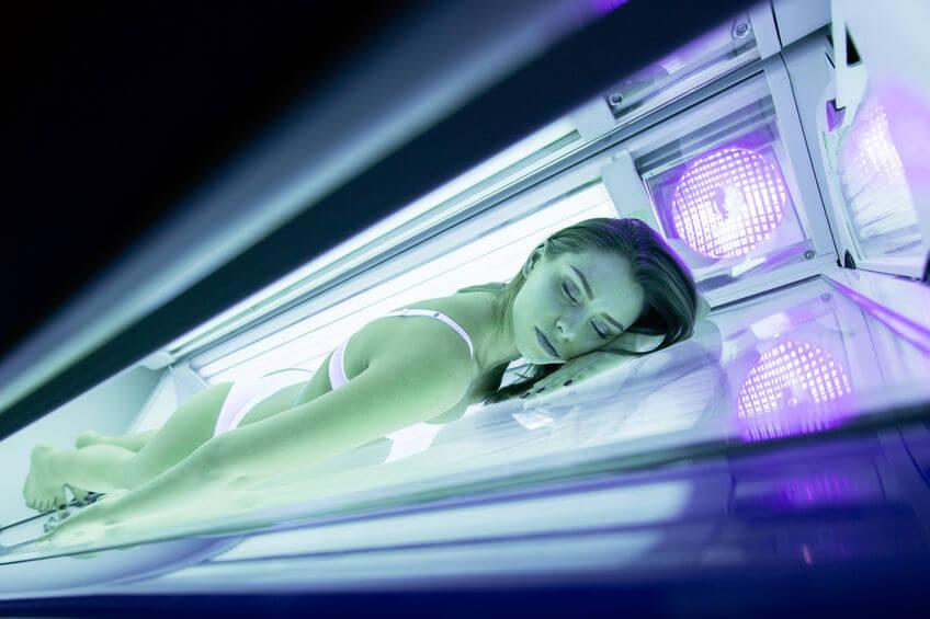 žena brunetka leží na bruchu v soláriu