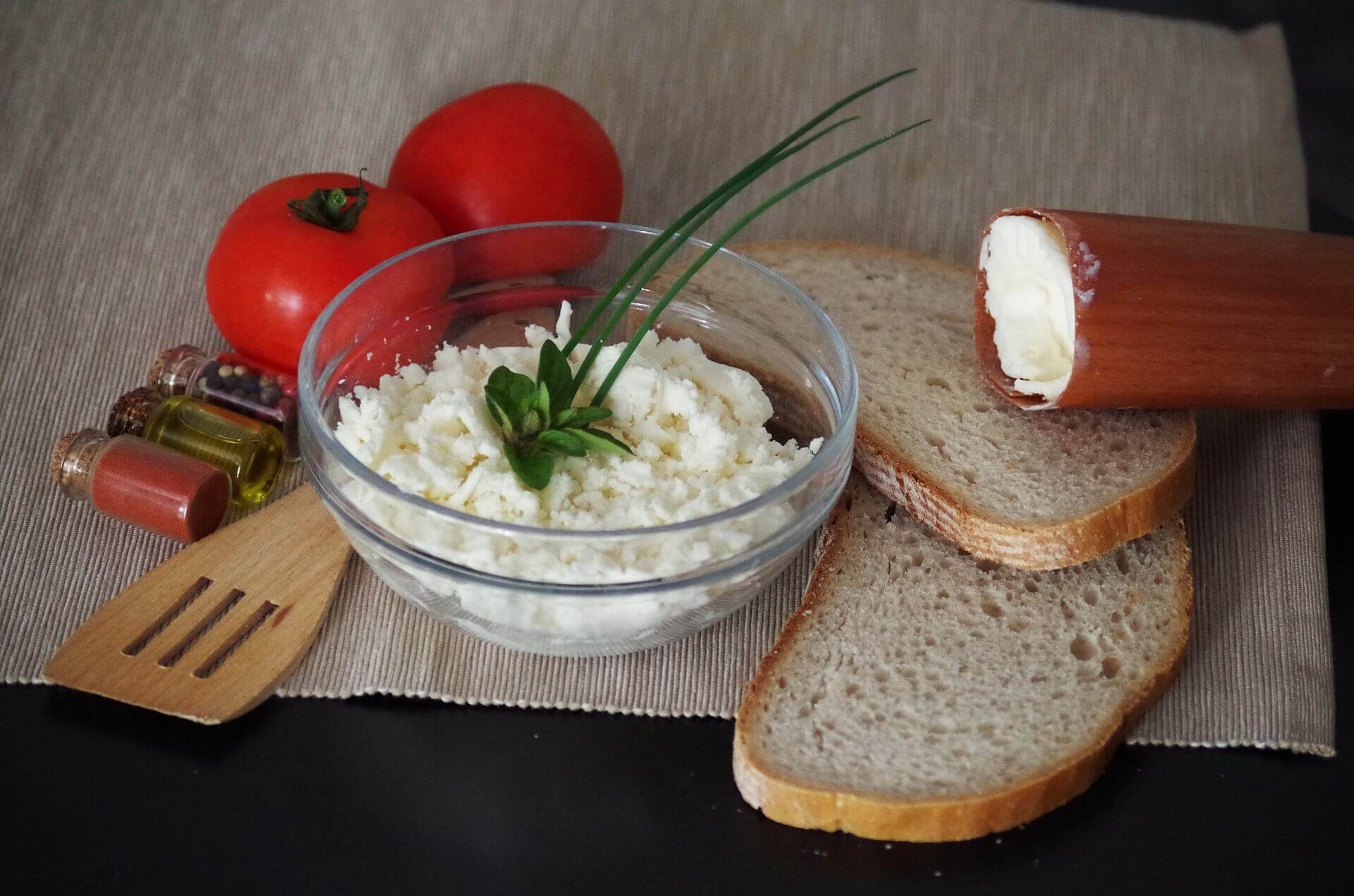 recepty z bryndze - bryndza v miske na stole s chlebom a paradajkami