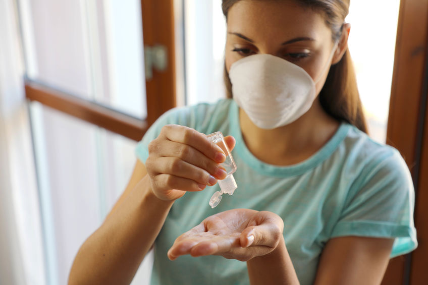 žena s rúškou na tvári si aplikuje antibakteriálny gél na ruky, ako prevenciu pred baktériami a vírusmi