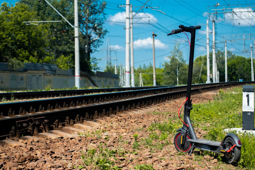 Elektrokolobežka pri vlakovej trati.