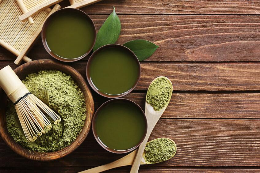 Prášok henna v zelenom odtietni v miske a na drevených lyžičkách.