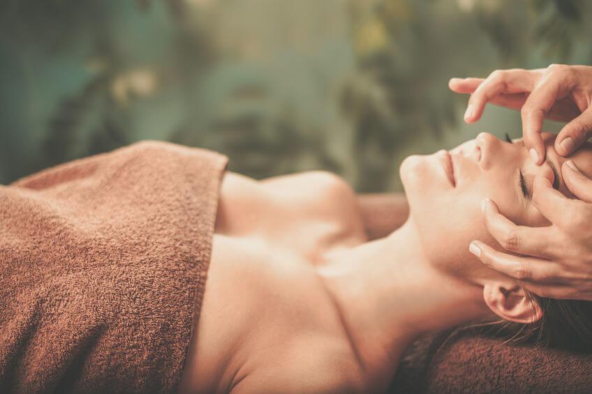 Žena dostáva masáž tváre v spa.