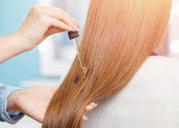 Aplikácia ricínového oleja na vlasy.