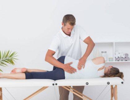 Doktor vyštrujúci ženu na bolesť krížov / chrbta.