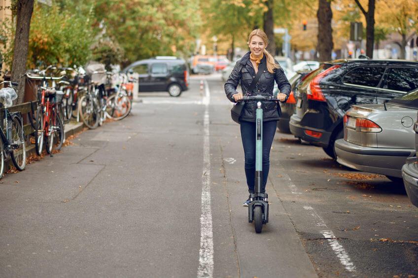 Žena jazdiaca po meste na elektrokolobežke.