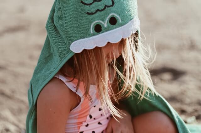 Malé dievčatko sediace na pláži, chrániace sa pred horúcimi letnými slnečnými lúčmi.