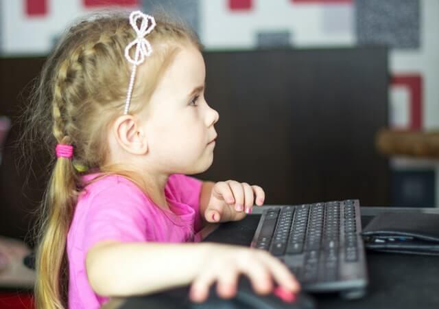 Malé dievčatko namiesto trávenia času vonku sa hrá na počítači.
