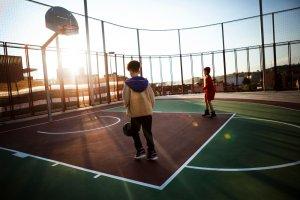 Deti hrajúce sa vonku basketbal.