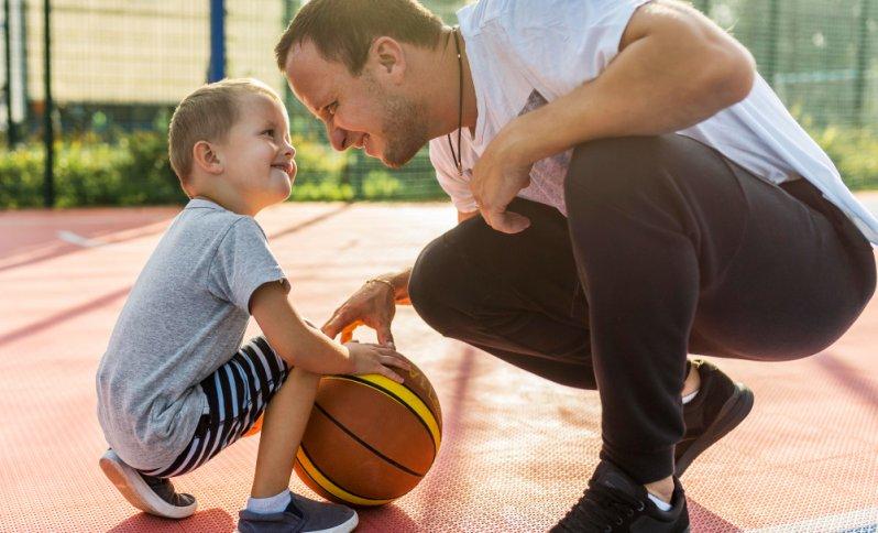 Otec so synčekom hrajú na dvore basketbal.