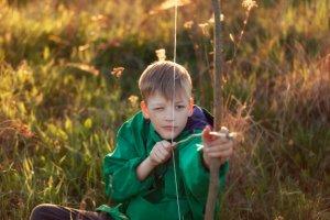 Malý chlapec v poli sa snaží trafiť terč z luku.