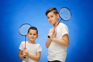 Dvaja malí chlapci čo držia badmintonové rakety.