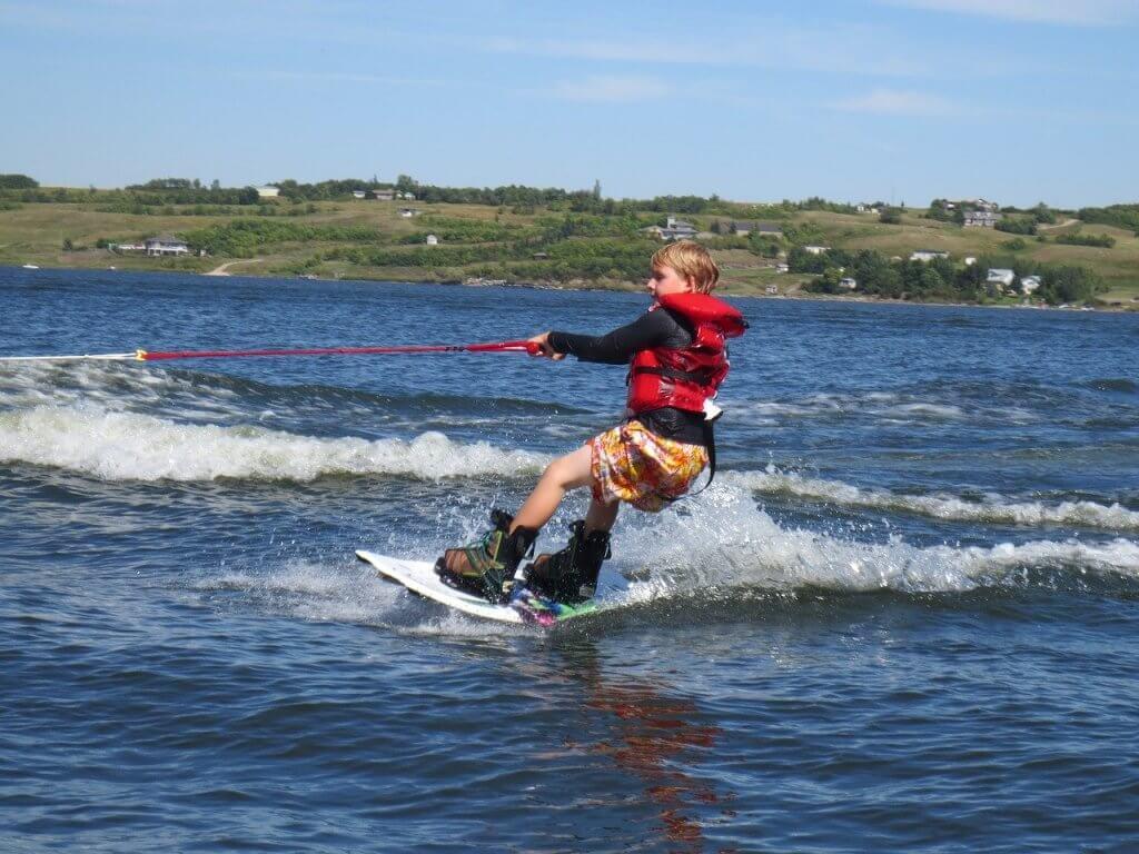 Malý chlapec počas dovolenky športuje wakeboarding.