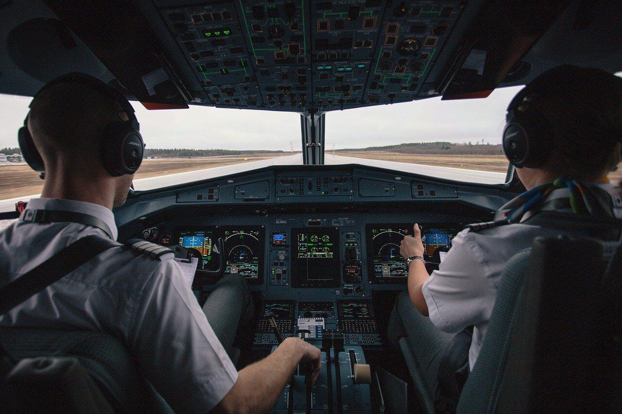 Fotka dvoch pilotov z cockpitu malého lietadla pri vzlete na nebo.