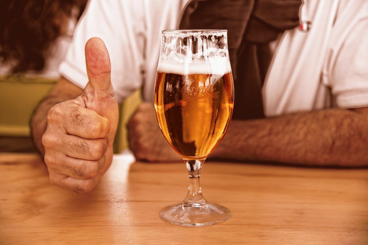 Fotografia muža v bare s pivom na stole.