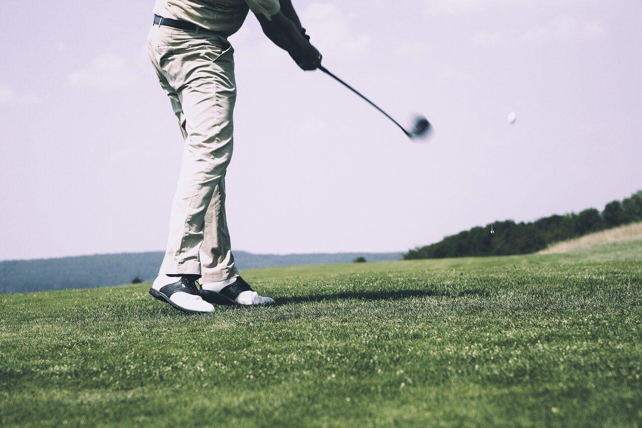 Starší muž hrajúci golf na golfovom ihrisku.