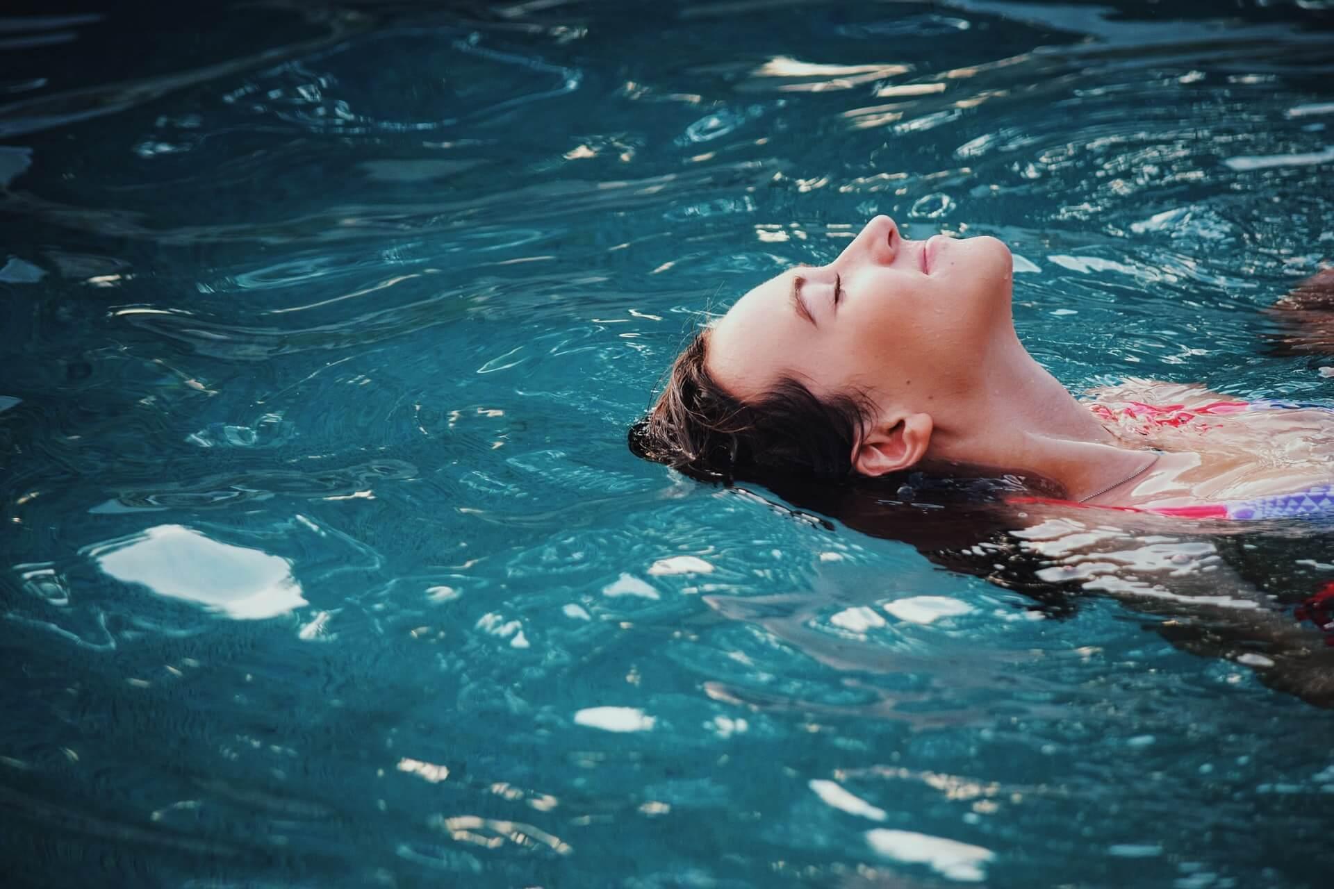 Žena splývajúca na vode v bazéne počas leta.