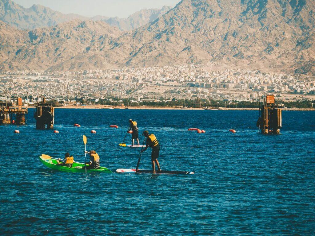 Ľudia športujúci paddleboarding na vode.