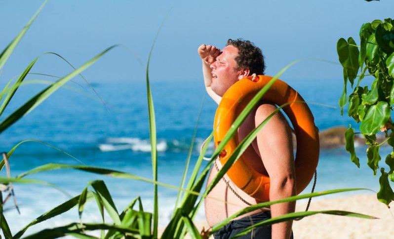 Muž s kolesom na pláži, ktorému je veľmi horúco.