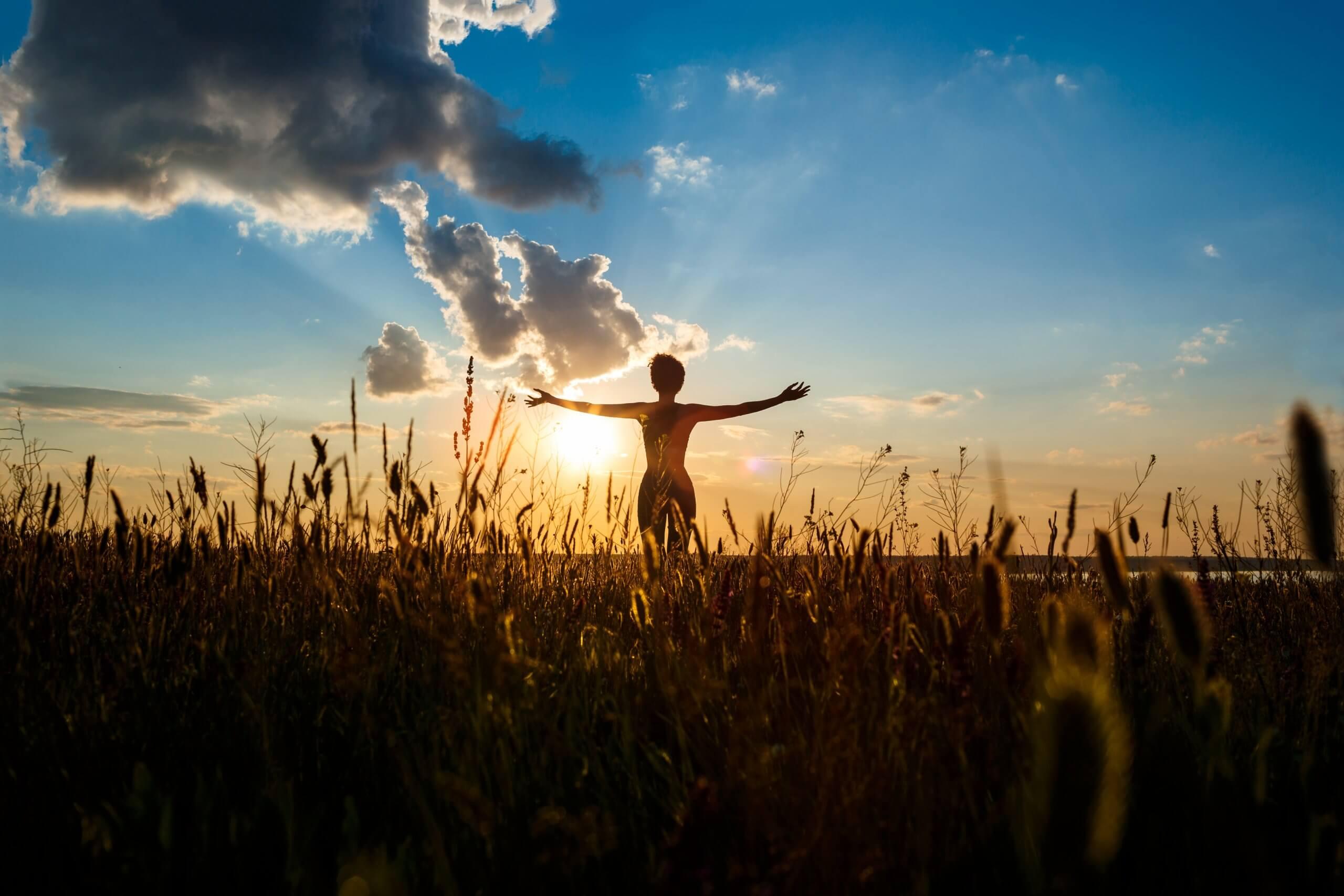 Žena cvičiaca jogu pri západe slnka na poli.
