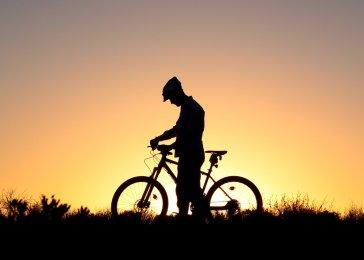 Fotografia cyklistu pri západe slnka.