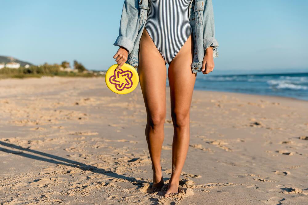 Žena na pláži, ktorá drží fribee.
