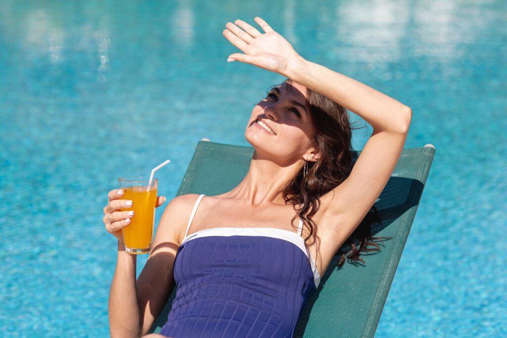 Mladá žena s drinkom, ktorá oddychuje na lehátku.