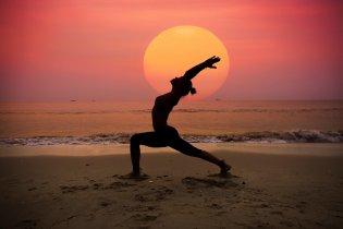 Žena cvičiaca jogu na pláži pri mori pri západe slnka.